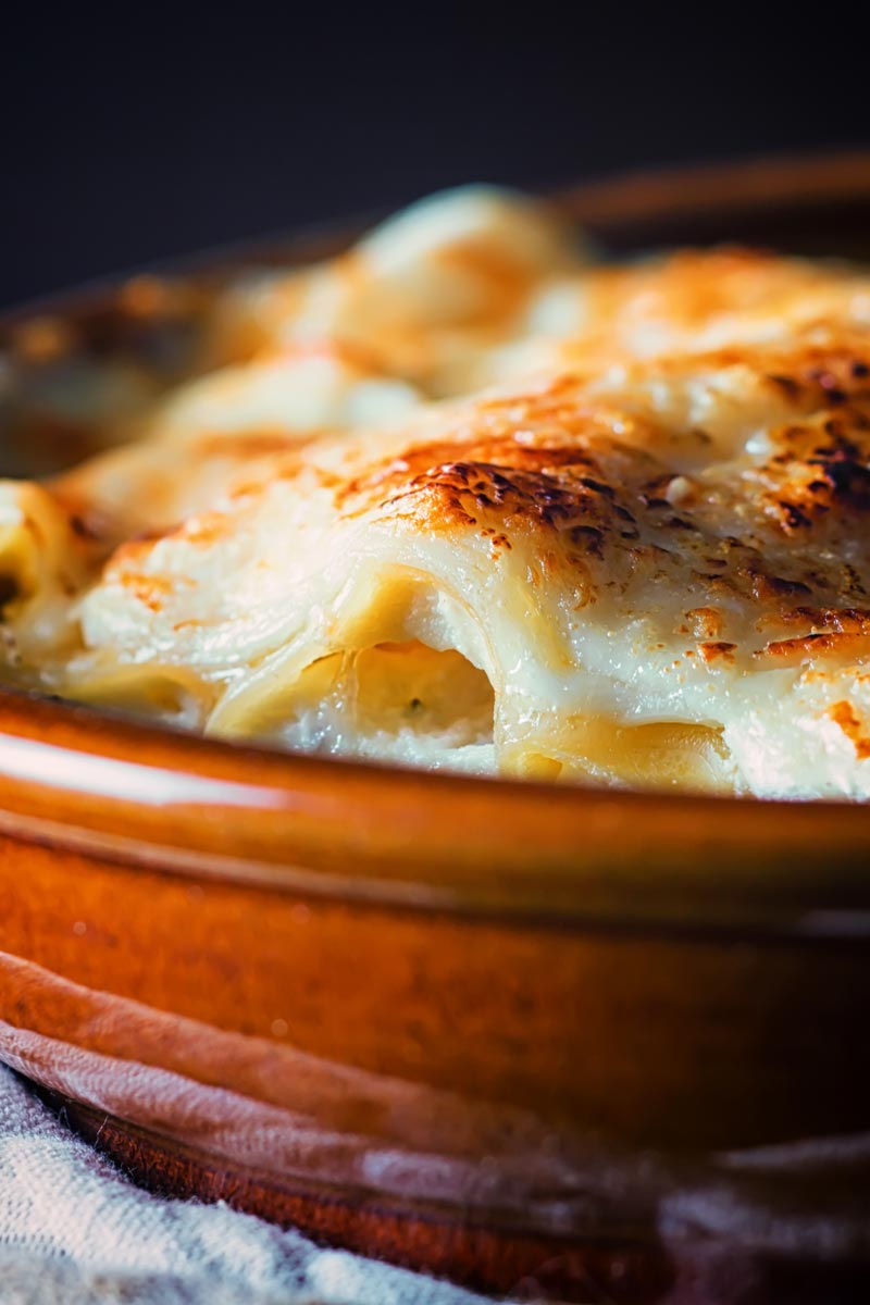 Portrait close up image of cauliflower cannelloni with a cheesy topping served in an earthenware bowl against a dark backdrop