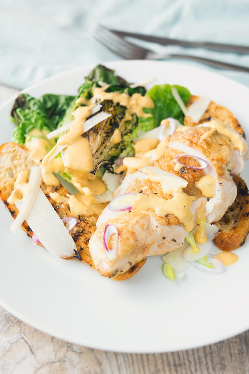 Portrait image of a chicken Caesar Salad served on a white plate featuring a roast chicken breast, seared baby gem lettuce hearts, ciabatta croutons and parmesan shavings
