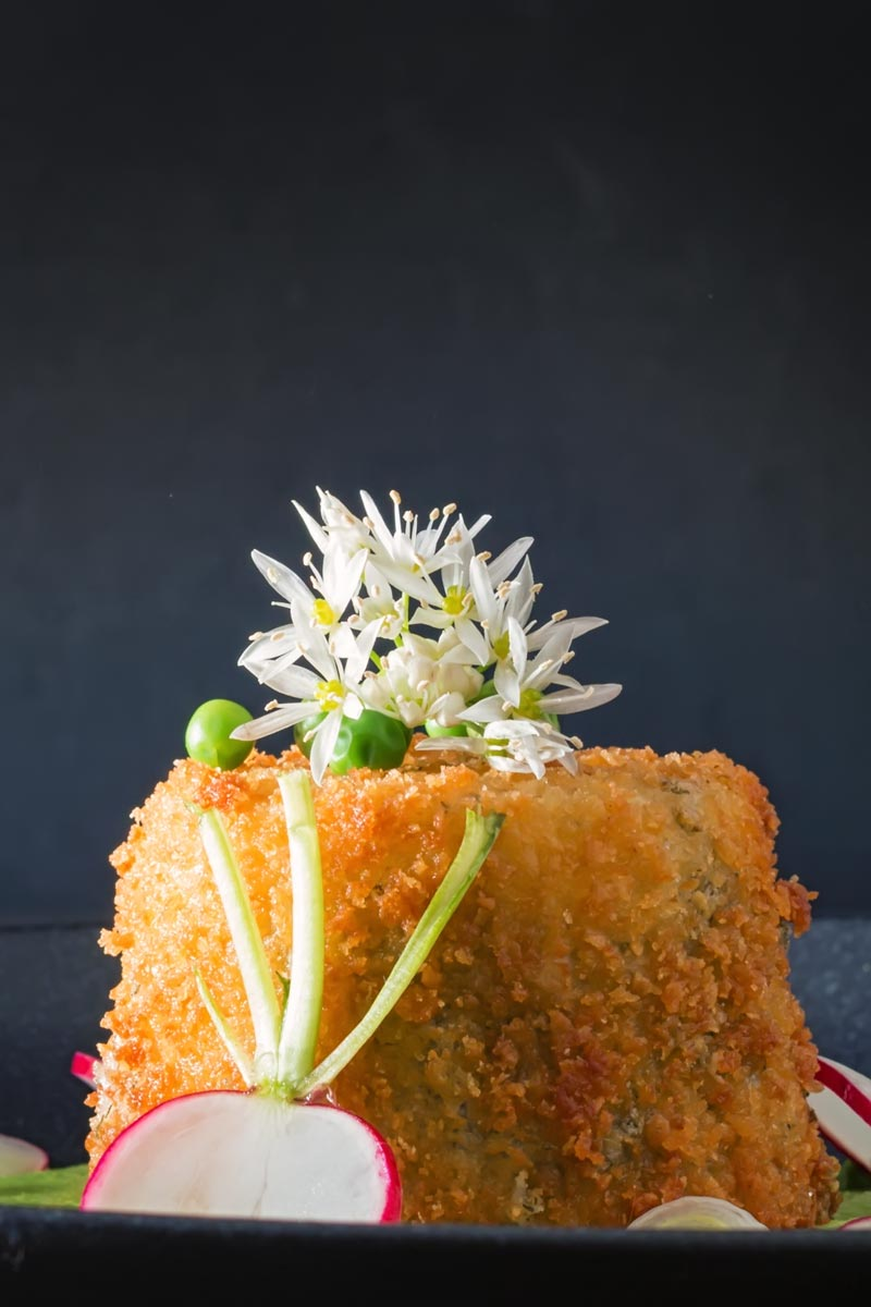 Portrait image of golden deep fried goats cheese with garlic flowers and sliced radish