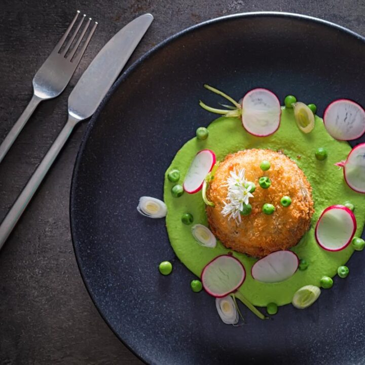 Square overhead image of golden deep fried goats cheese, served on pea puree with garlic flowers , sliced radish, peas and spring onions