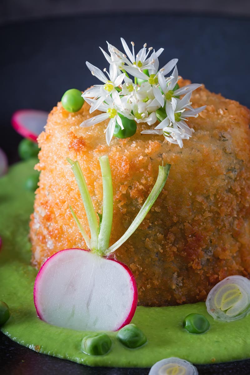 Portrait image of golden deep fried goats cheese, served on pea puree with garlic flowers , sliced radish, peas and spring onions