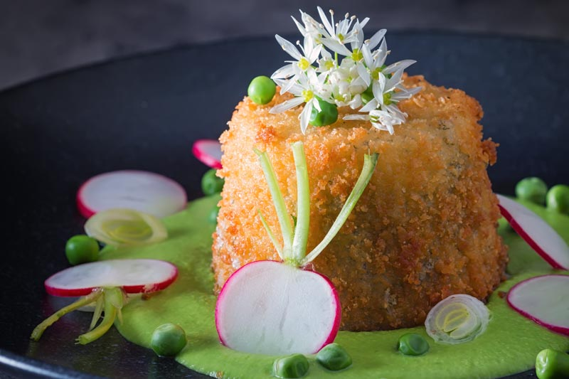 Landscape image of golden deep fried goats cheese, served on pea puree with garlic flowers , sliced radish, peas and spring onions