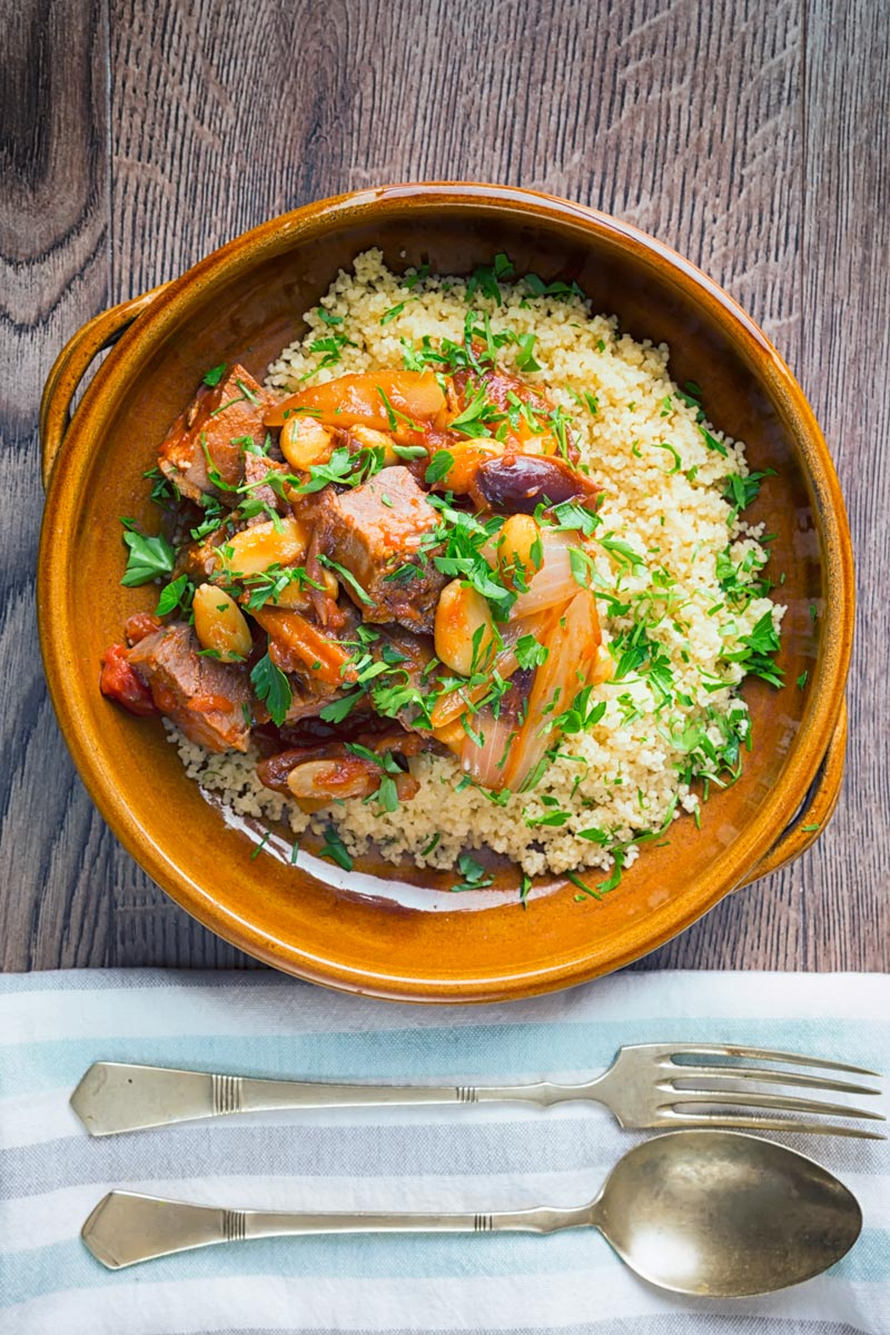 Portrait overhead image of a duck tagine with almonds and dates served on buttered couscous in an earthenware bowl