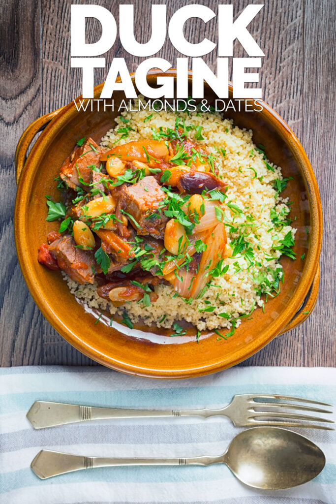 Portrait overhead image of a duck tagine with almonds and dates served on buttered couscous in an earthenware bowl with text