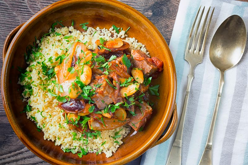 Landscape overhead image of a duck tagine with almonds and dates served on buttered couscous in an earthenware bowl