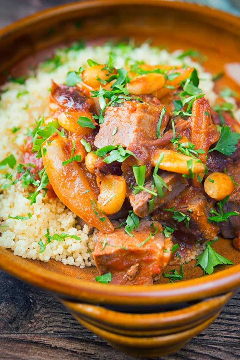 Close up portrait image of a duck tagine with almonds and dates served on buttered couscous in an earthenware bowl