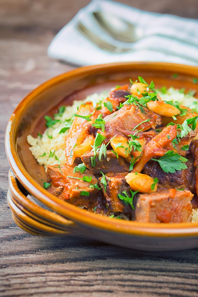 Portrait image of a duck tagine with almonds and dates served on buttered couscous in an earthenware bowl