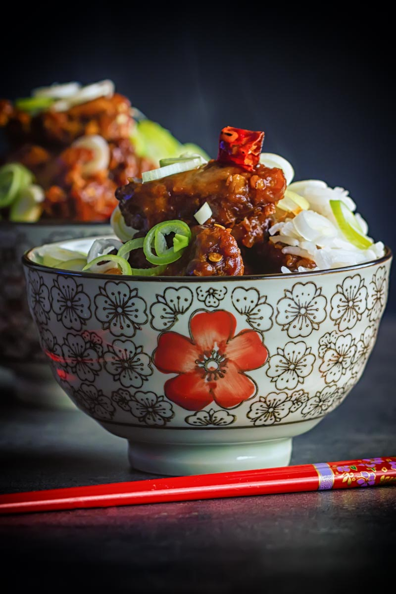 Portrait image of General Tso's chicken served in two small bowls decorated with a red flower with Asian styling and red chopsticks