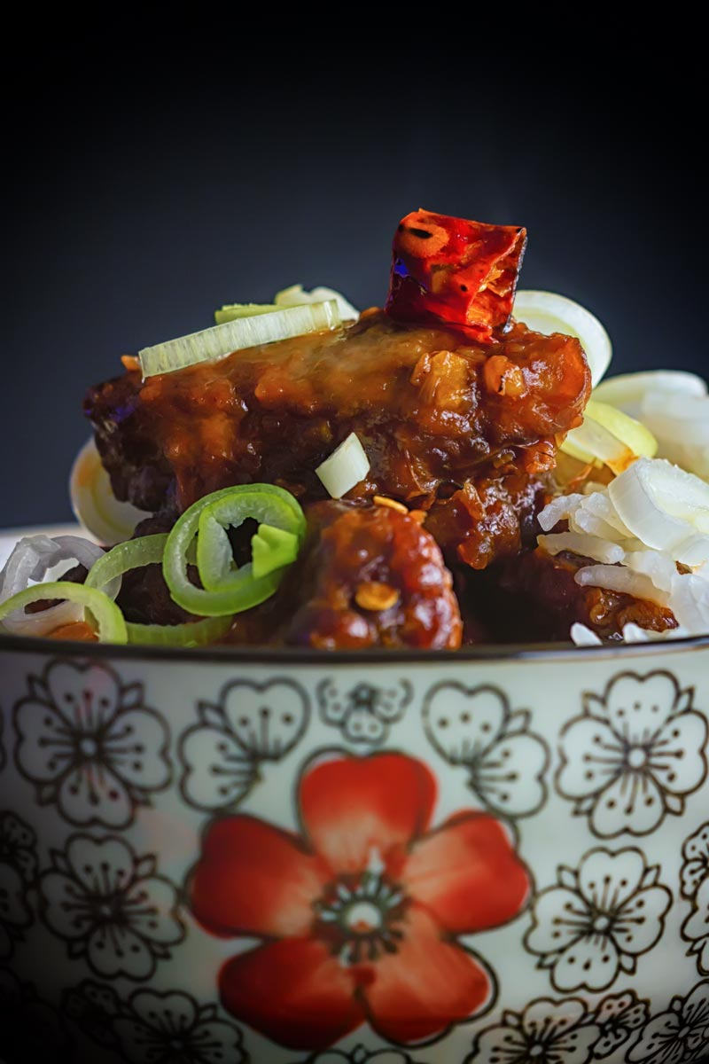 Close up portrait image of General Tso's chicken served in a bowl decorated with a red flower with Asian styling