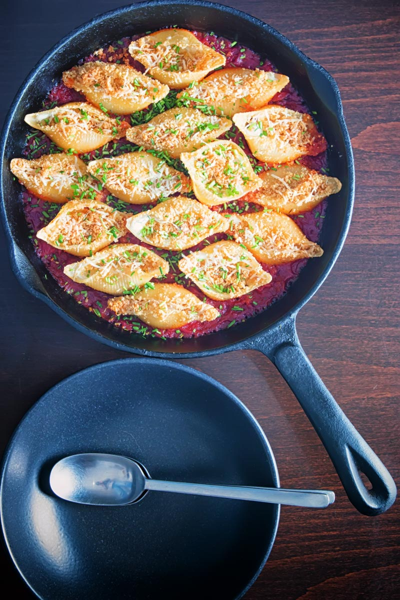 Portrait overhead image of Goats Cheese Stuffed Pasta Shells cooked and served in a cast iron skillet