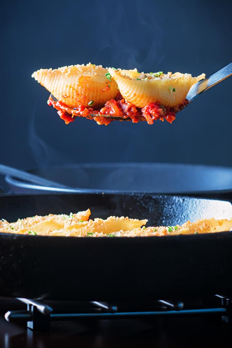 Portrait image of Goats Cheese Stuffed Pasta Shells served in a cast iron pan with two steaming pasta shells on a serving spoon