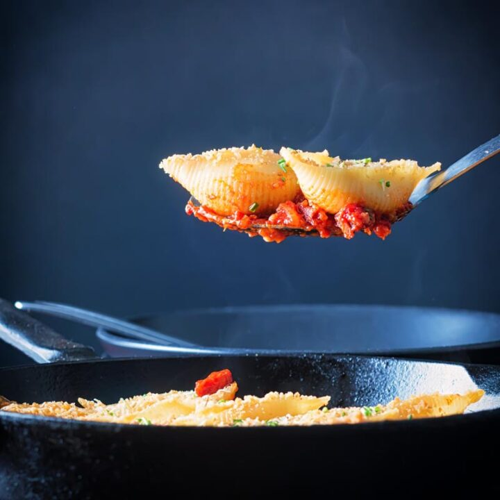 Square image of Goats Cheese Stuffed Pasta Shells served in a cast iron pan with two steaming pasta shells on a serving spoon