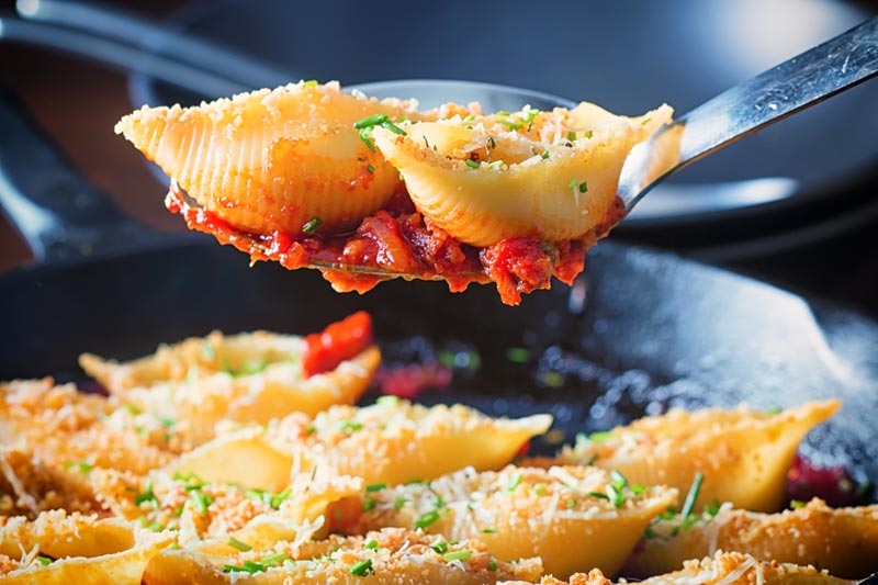 Landscape image of Goats Cheese Stuffed Pasta Shells served in a cast iron pan with two pasta shells on a serving spoon