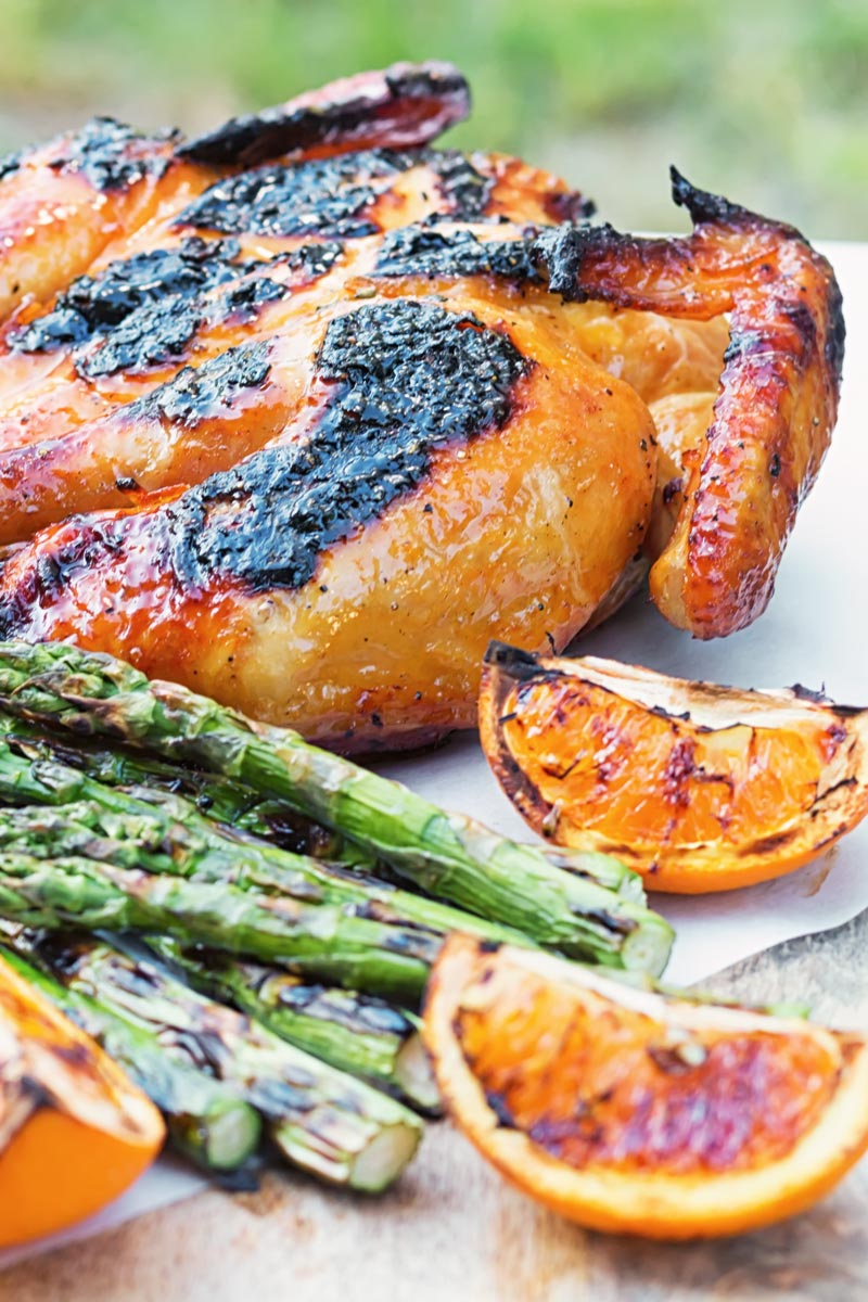Portrait image of a Grilled Spatchcock Chicken served on a wooden chopping board with asparagus and grilled orange segments