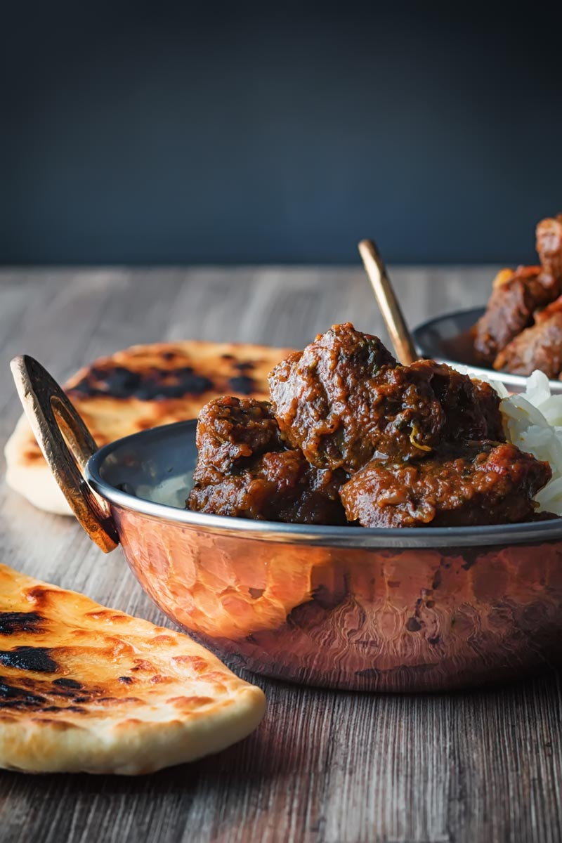 Portrait image of a beef vindaloo curry served in a copper coated curry bowl with a naan bread served on a rustic wooden table top