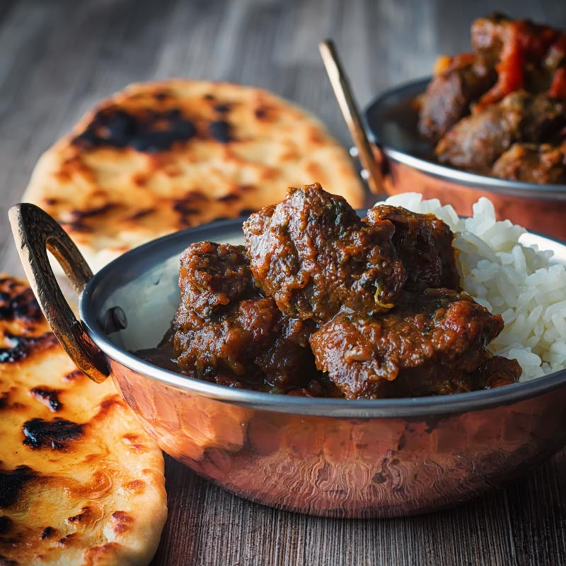 Square image of a beef vindaloo curry served in a copper coated curry bowl with a naan bread served on a rustic wooden table top
