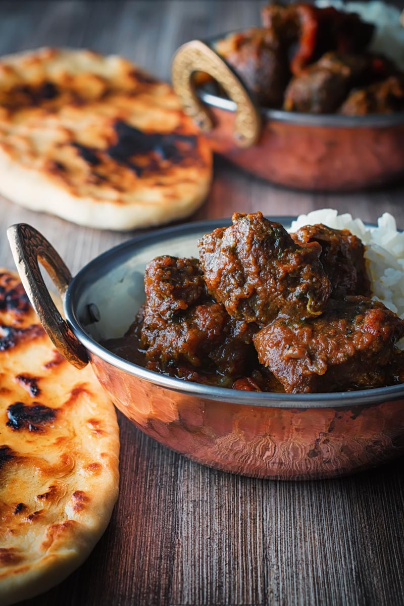 Portrait image of a beef vindaloo curry served in two copper coated curry bowls with a naan bread served on a rustic wooden table top
