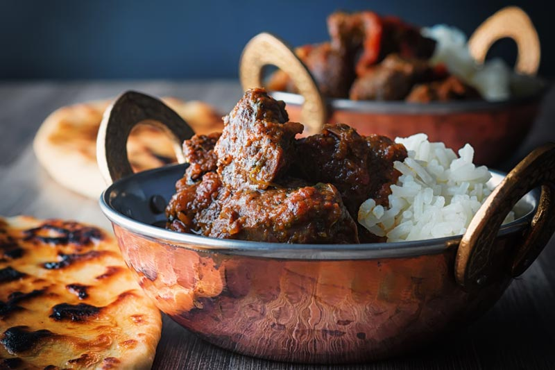 Landscape image of a beef vindaloo curry served in two copper coated curry bowls with a naan bread served on a rustic wooden table top