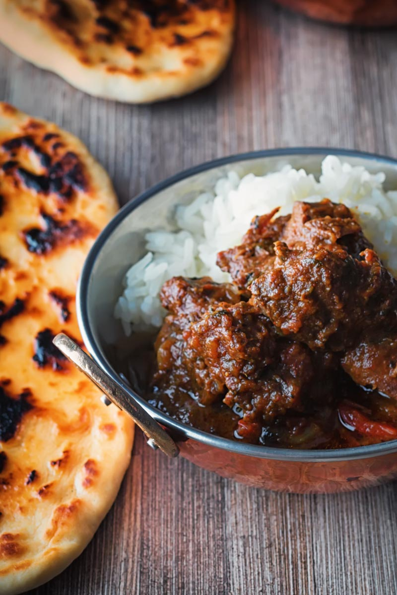 Portrait image of a beef vindaloo curry served in a copper coated curry bowls with a naan bread served on a rustic wooden table top taken from a high angle