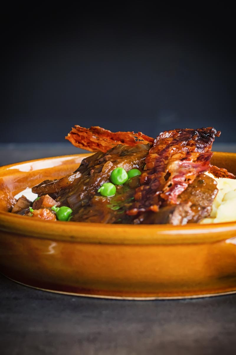 Portrait image of liver and onions with crispy bacon, mashed potatoes and peas and onion gravy served in an earthenware bowl