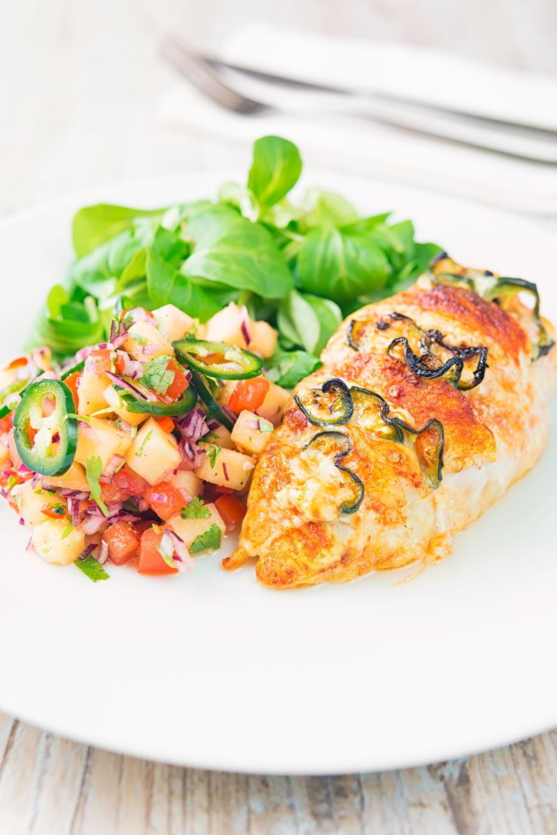 Portrait image of a roasted jalapeño and cheddar cheese stuffed chicken breast served on a white plate with pineapple salsa and a green salad