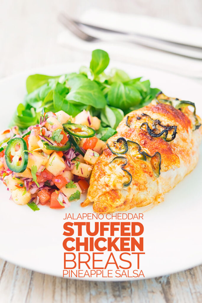 Portrait image of a roasted jalapeño and cheddar cheese stuffed chicken breast served on a white plate with pineapple salsa and a green salad with text