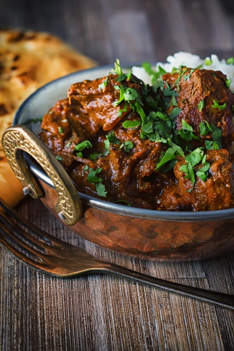 Portrait image of a lamb rogan josh curry served in a copper coated curry bowl with a naan bread