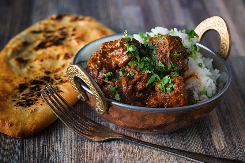 Landscape image of a lamb rogan josh curry served in a copper coated curry bowl with a naan bread