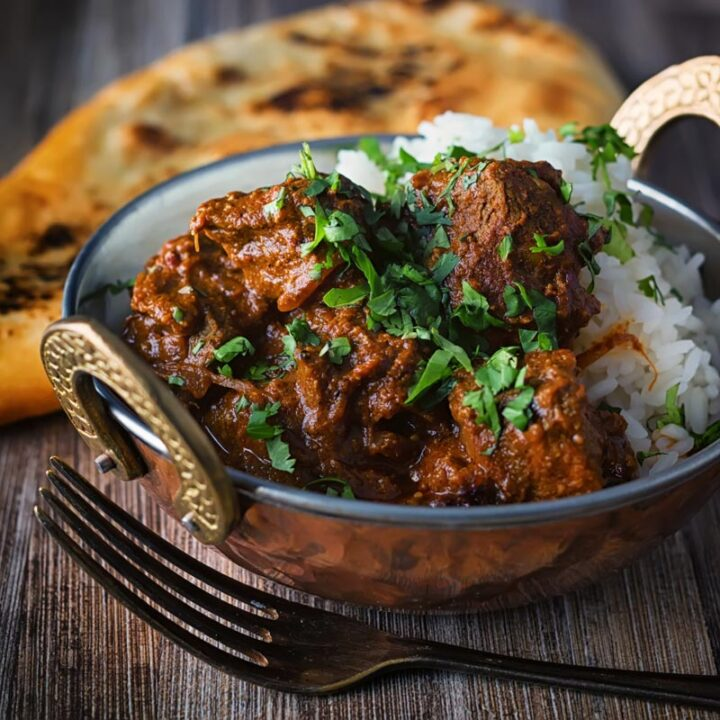 Square image of a lamb rogan josh curry served in a copper coated curry bowl with a naan bread