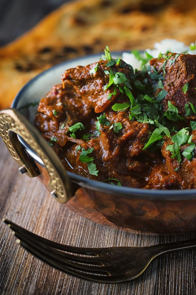 Portrait close up image of a lamb rogan josh curry served in a copper coated curry bowl with a naan bread
