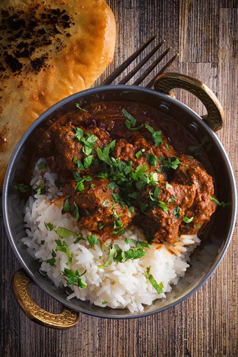 Portrait overhead image of a lamb rogan josh curry served in a copper coated curry bowl with a naan bread