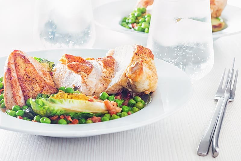 Landscape image of petits pois a la Francaise served in a white bowl with a sliced roast chicken breast on a bright backdrop with iced water