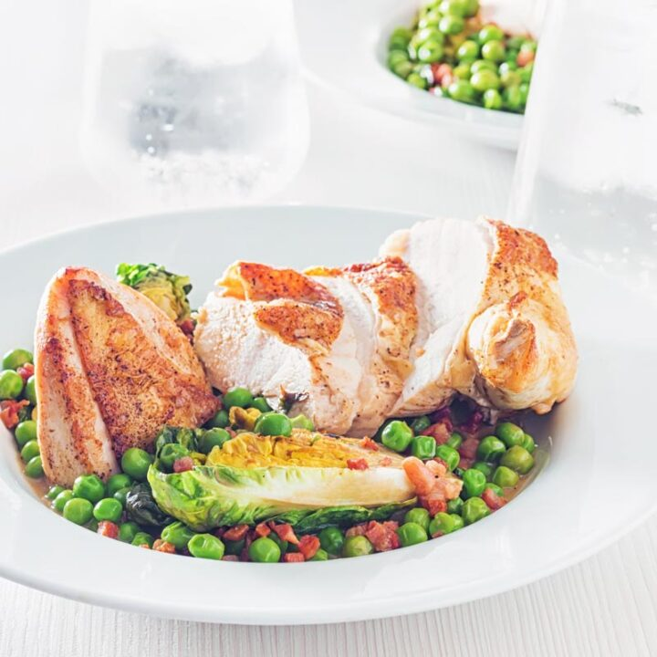 Square image of petits pois a la Francaise served in a white bowl with a sliced roast chicken breast on a bright backdrop with iced water