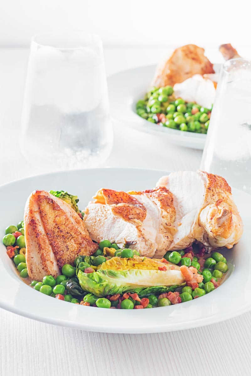 Portrait image of petits pois a la Francaise served in a white bowl with a sliced roast chicken breast on a bright backdrop with iced water