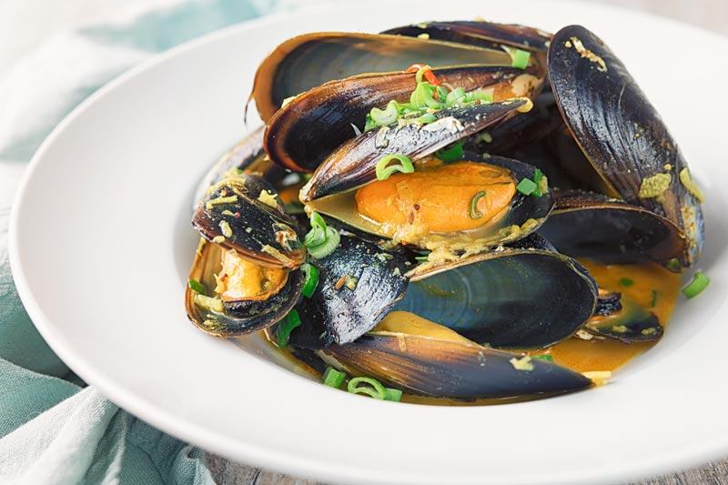 Landscape image of an Indian curry mussels served in a white bowl with a coconut broth and spring onions