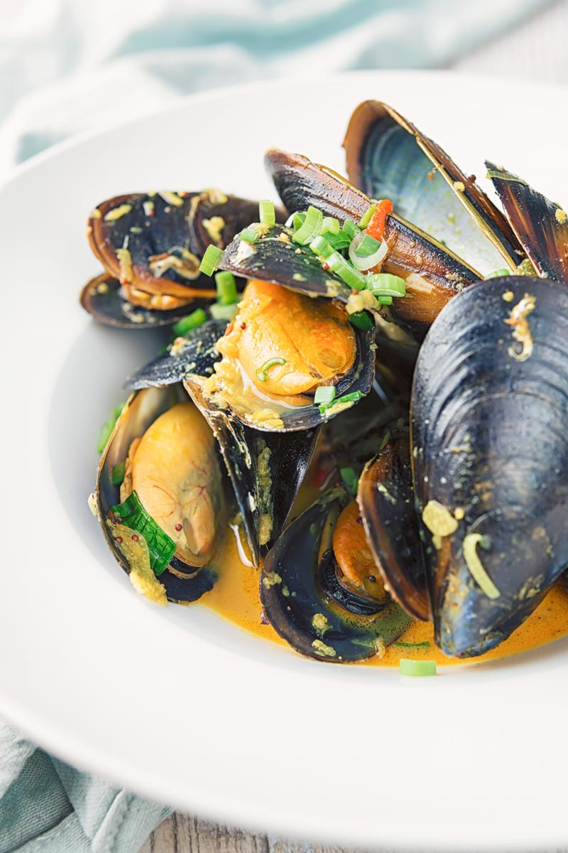 Portrait image of an Indian curry mussels served in a white bowl with a coconut broth and spring onions