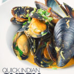 Portrait image of an Indian curry mussels served in a white bowl with a coconut broth and spring onions with text