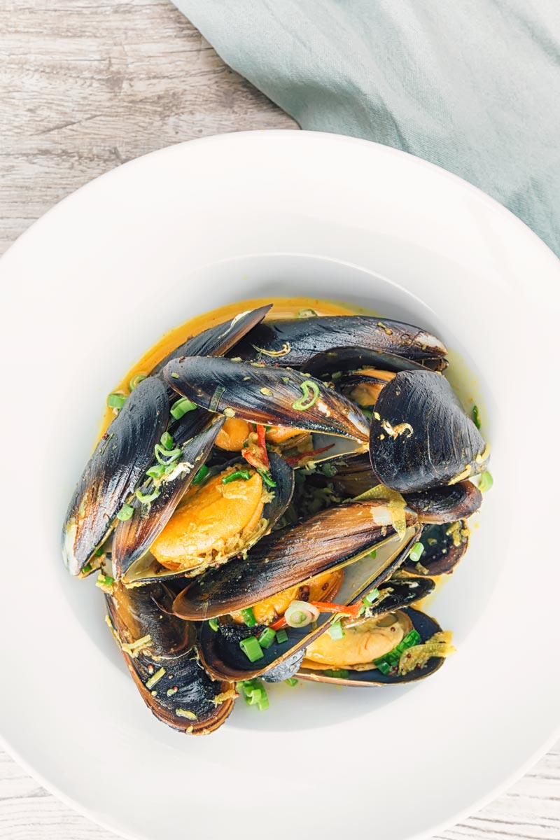 Portrait overhead image of an Indian curry mussels served in a white bowl with a coconut broth and spring onions