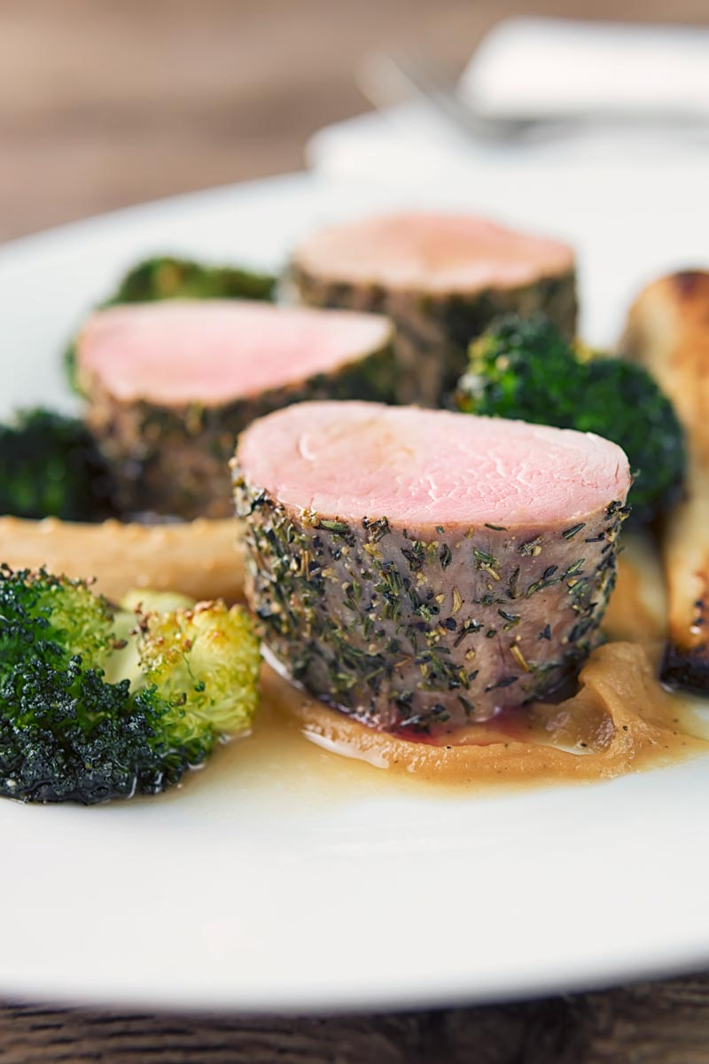Close up portrait image of pink roast pork fillet served presented attractively on a white plate with apple puree, roast broccoli and parsnips and a cider sauce