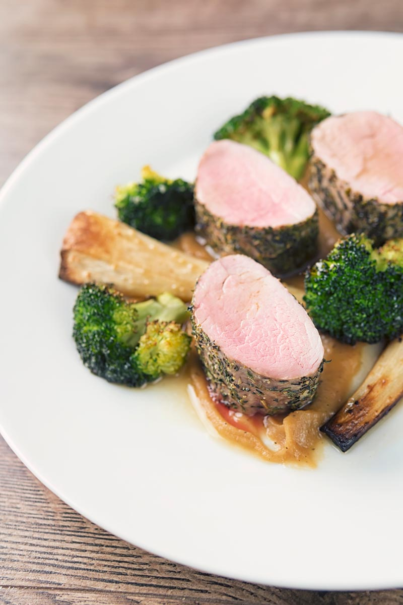 Portrait image of pink roast pork fillet served presented attractively on a white plate with apple puree, roast broccoli and parsnips and a cider sauce