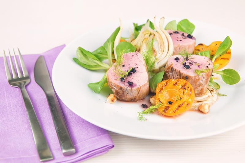 Landscape image of pink roast pork tenderloin with seared apricots and fennel served with Tasmanian pepper served ona white plate with purple linen