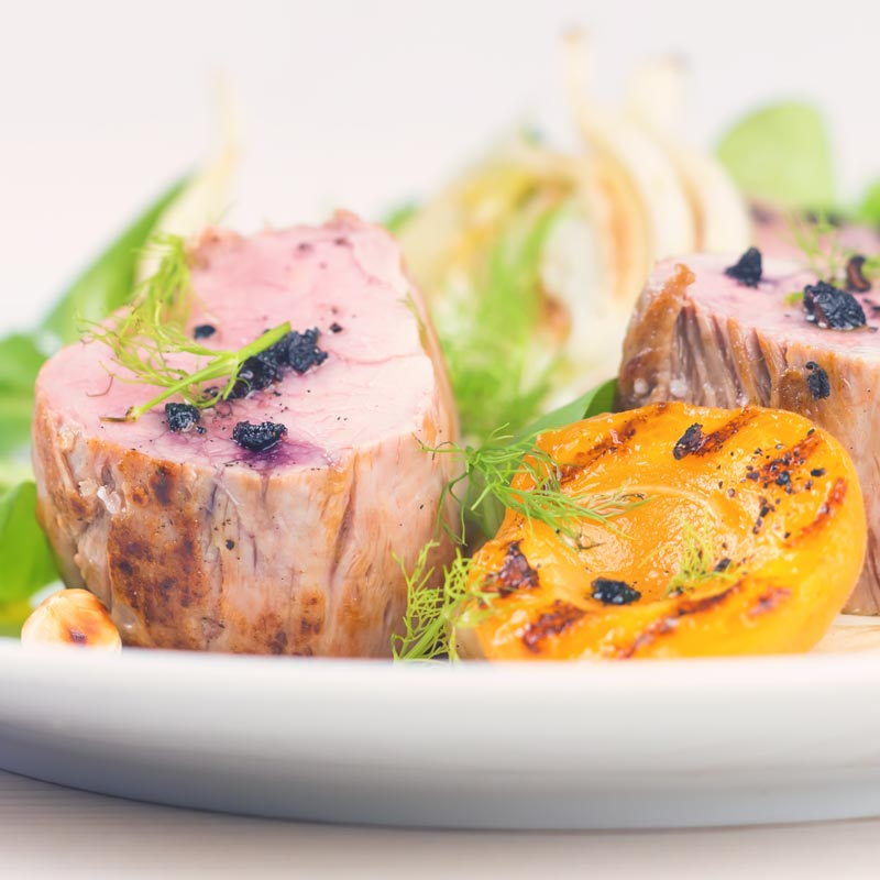 Square image of pink roast pork tenderloin with seared apricots and fennel served with Tasmanian pepper served ona white plate with purple linen