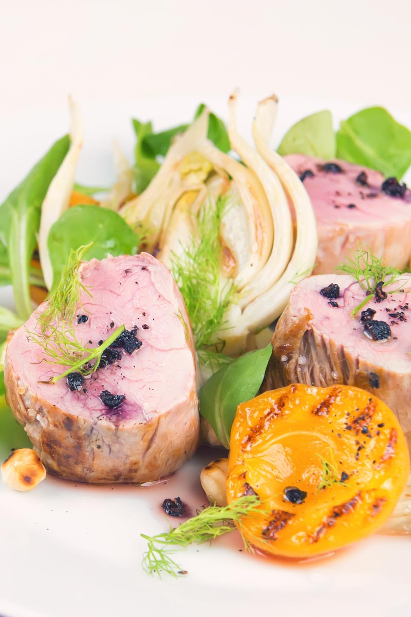 Portrait image of pink roast pork tenderloin with seared apricots and fennel served with Tasmanian pepper served ona white plate with purple linen