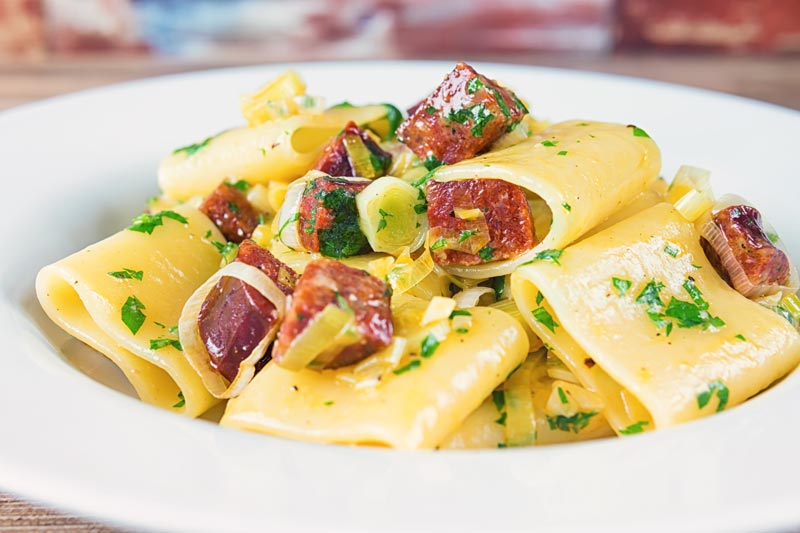 Landscape image of a leek and salami pasta with paccheri pasta served in a white bowl