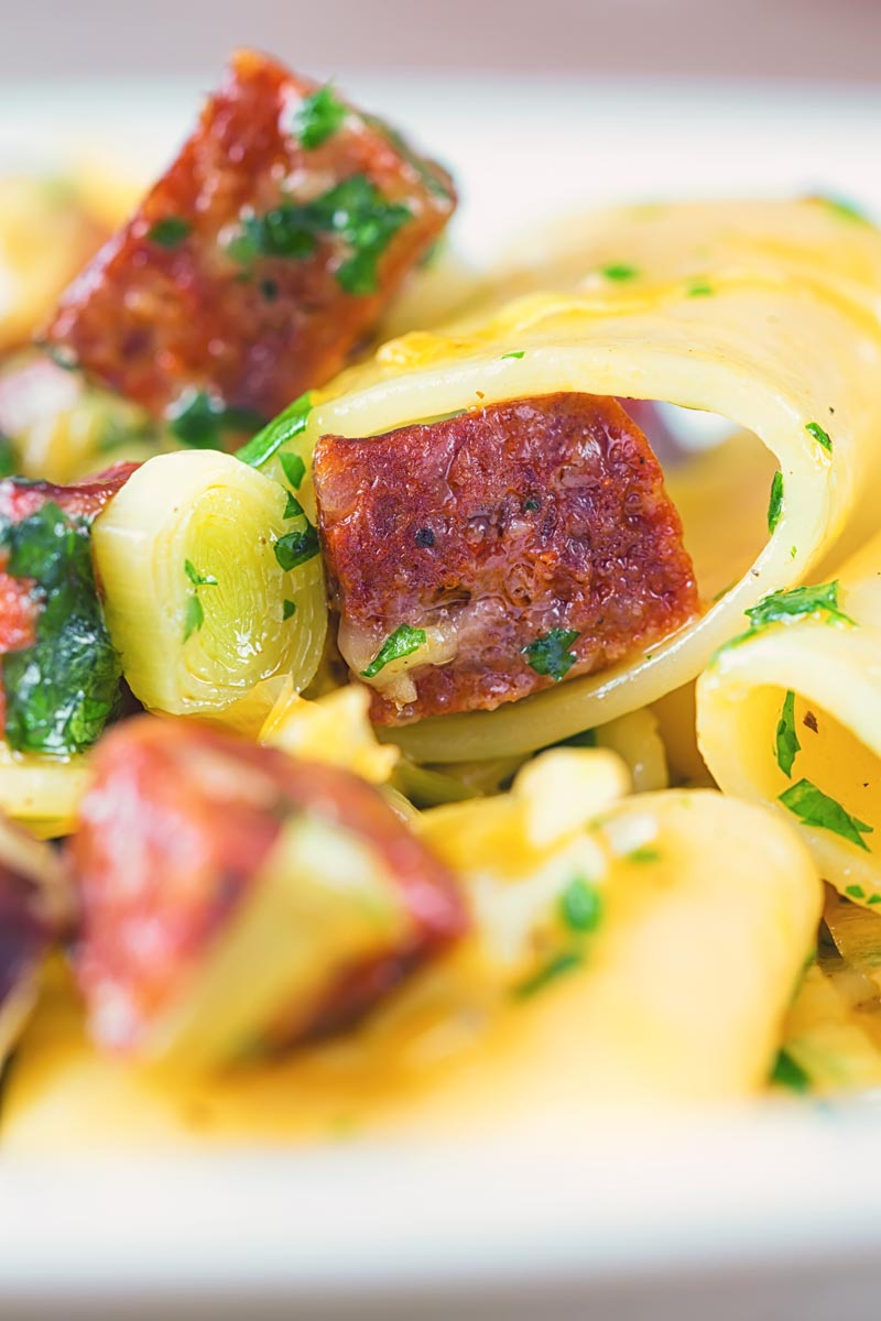 Close up portrait image of a leek and salami pasta with paccheri pasta served in a white bowl