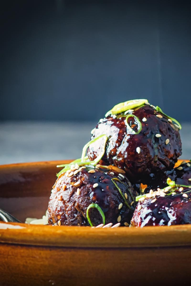 Portrait close up image of sticky teriyaki meatballs served with wholegrain rice in an earthenware bowl with a vintage fork