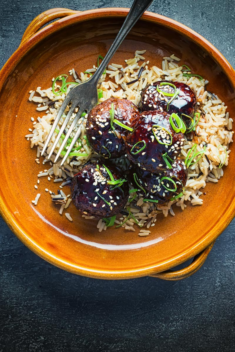 Portrait overhead image of sticky teriyaki meatballs served with wholegrain rice in an earthenware bowl with a vintage fork