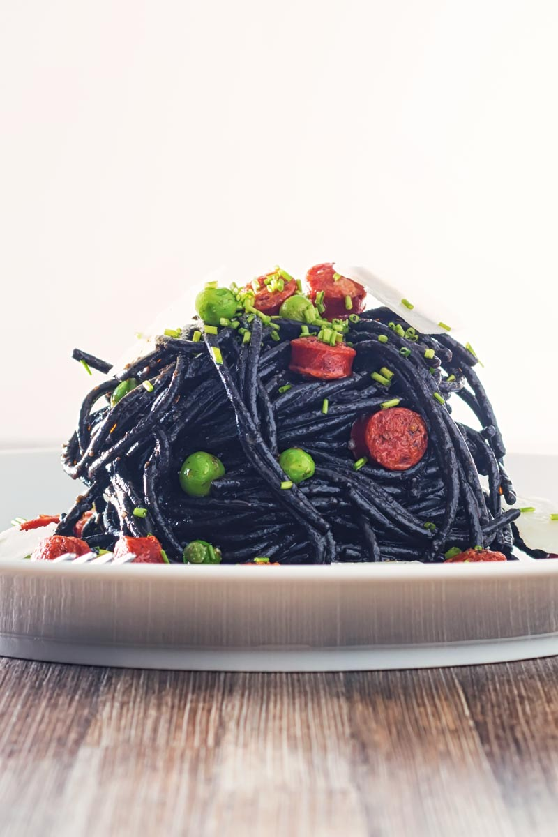 Portrait image of a tall pine of squid ink spaghetti on a white plate served with peas, pepperoni and parmesan cheese shavings on a wooden table