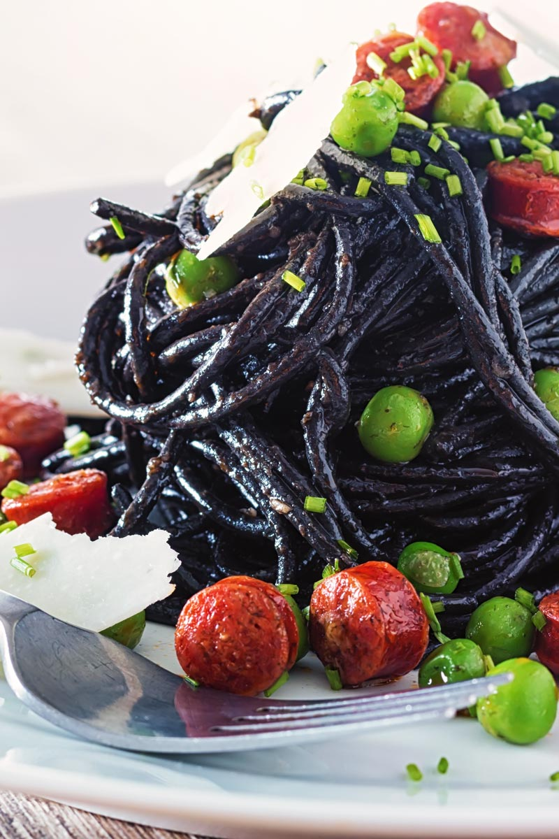 Close up portrait image of a tall pine of squid ink spaghetti on a white plate served with peas, pepperoni and parmesan cheese shavings