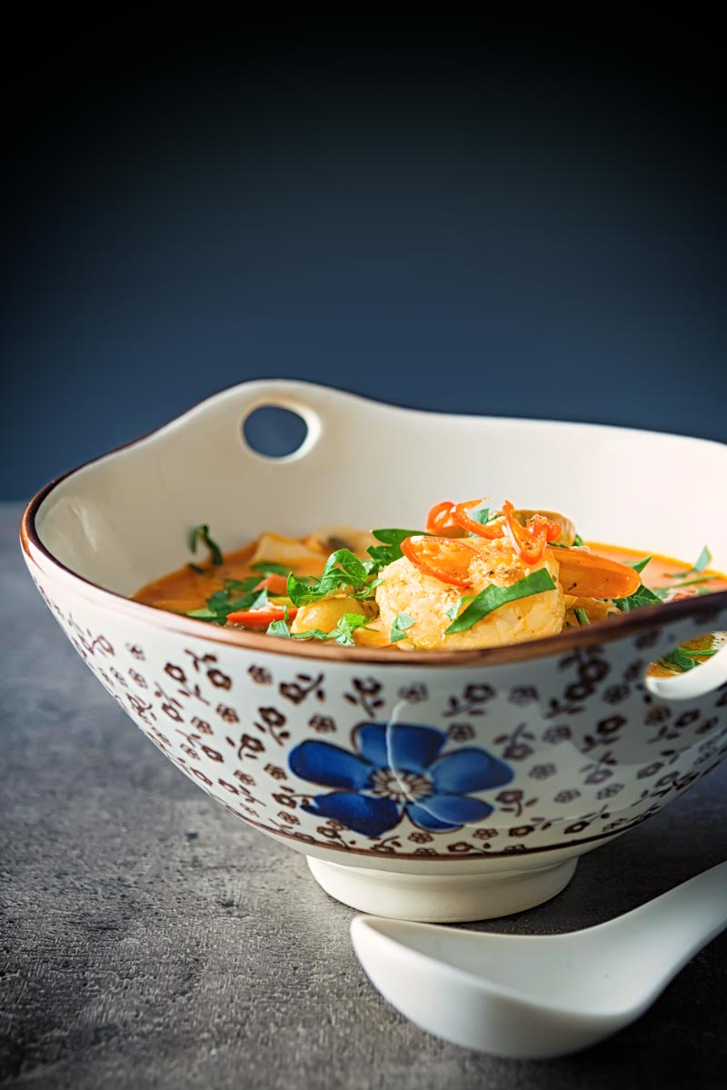 Portrait image of a Tom Yum Soup served in an Asian style soup bowl decorated with a blue flower in a dark setting